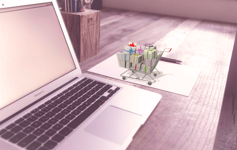 Un computer e un carrello della spesa che rappresentano come la scrittura ottimizzata di schede prodotto ecommerce sia fondamentale per diminuire il volume dei resi e risolver e problemi logistici