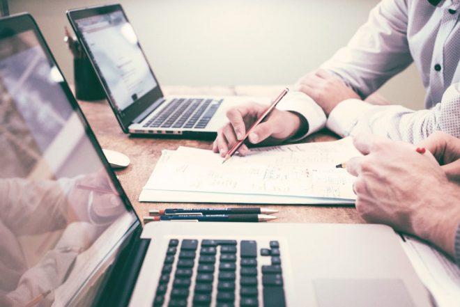 Una scrivania con due computer portatili, su cui si intravedono due persone intente a scrivere e progettare